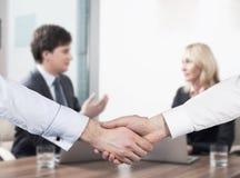 夫妇在业务会议上 握手作为成功的成交的概念 库存照片