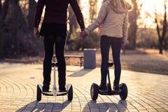 夫妇在举行手后面背面图的Gyroscooter乘坐电子滑行车户外秋天公园男人和妇女 图库摄影
