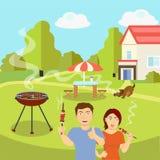 夫妇在乡间别墅附近油煎烤肉 免版税库存照片