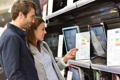 夫妇在买新的电视的超级市场 库存图片