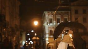 夫妇在亲吻在夜城市街道上的雨下的努瓦尔减速火箭的服装穿戴了,掩藏从雨在伞下 影视素材