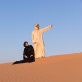 夫妇在传统阿拉伯衣物穿戴了在沙漠 免版税库存照片