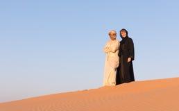 夫妇在传统阿拉伯衣物穿戴了在沙漠 库存图片
