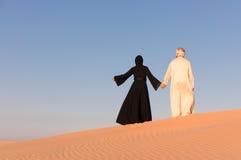 夫妇在传统阿拉伯衣物穿戴了在沙漠 免版税图库摄影