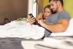 年轻夫妇在使用一种数字式片剂的床上 免版税库存照片