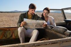 夫妇在公路车辆的读书地图 免版税库存照片