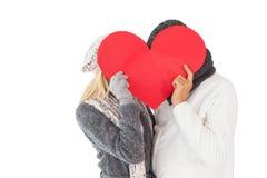 夫妇在冬天塑造摆在与心脏形状 免版税库存图片