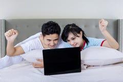 夫妇在卧室的用途膝上型计算机 免版税库存照片