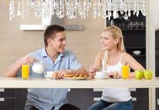 夫妇在厨房里吃 免版税库存图片