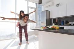 年轻夫妇在厨房,恋人西班牙人运载亚裔妇女现代公寓 免版税图库摄影