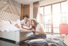 夫妇在地板上的包装手提箱在屋子查寻旅行旅行网上薪水的用途片剂里由信用卡 库存照片