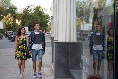 夫妇在城市附近微笑并且走,并且去购物,秋天和春天 免版税库存图片