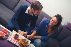 年轻夫妇在客厅准备吃薄煎饼 免版税库存照片