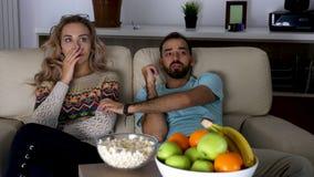 夫妇在客厅观看在长沙发的一部可怕电影 股票录像