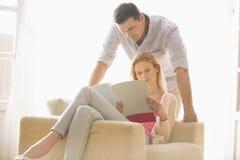 夫妇在家一起读书杂志 免版税库存图片