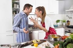 年轻夫妇在家尖叫在厨房里 免版税库存照片