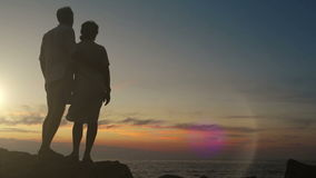 夫妇在岩石站立在握手的日落 股票视频