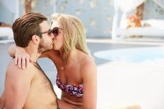 年轻夫妇在度假放松由游泳池的 图库摄影
