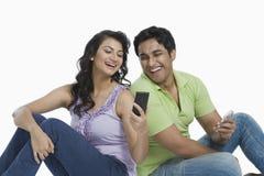 夫妇在手机的正文消息 免版税图库摄影