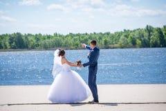 夫妇在新娘花束上把他们的手放 免版税库存照片