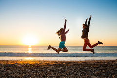 夫妇在日出的海滩跳跃 免版税库存图片