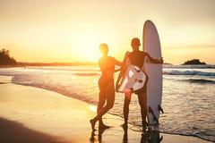 夫妇在日落海洋海滩的冲浪者逗留 免版税库存照片