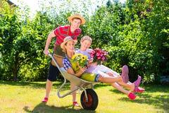 夫妇在有喷壶和手推车的庭院里 免版税图库摄影