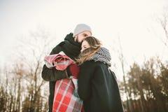 年轻夫妇在有格子花呢披肩和热水瓶的冬天森林里 图库摄影
