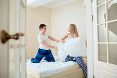夫妇在有的床上战斗在卧室把枕在 库存图片