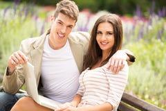 年轻夫妇在有膝上型计算机的一个公园 免版税图库摄影
