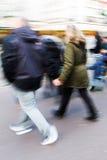 夫妇在有行动迷离的购物街道上走 库存图片