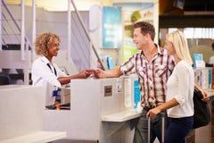 夫妇在机场登记离开在度假的书桌 免版税库存照片