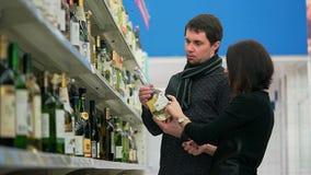 年轻夫妇在杂货店选择酒去拜访朋友 影视素材