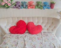 夫妇在椅子的心脏枕头 免版税库存照片