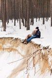 夫妇在毯子的冬天森林里在沙子悬崖 免版税库存照片