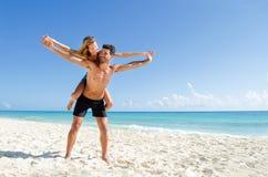 夫妇在海滩的肩扛乘驾 库存照片