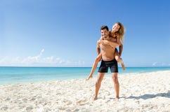 夫妇在海滩的肩扛乘驾 免版税图库摄影