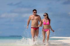 夫妇在海滩跑 图库摄影
