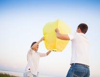 年轻夫妇在海附近发动一个黄色中国天空灯笼 免版税库存图片