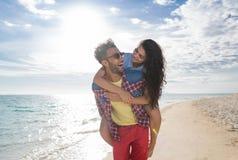 年轻夫妇在海滩暑假,愉快的微笑的人运载妇女后面海边 免版税库存图片