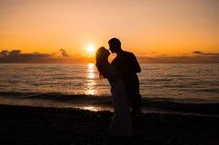 夫妇在海滩现出轮廓在日落 免版税库存图片
