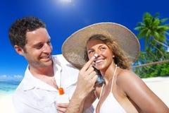 夫妇在海滩的太阳保护 免版税库存照片