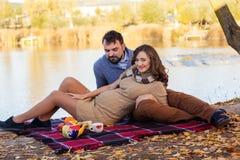 夫妇在湖,秋天时间附近坐 免版税库存图片