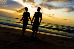年轻夫妇在热带海滩和日落的婚礼之日 免版税库存照片