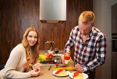 夫妇在烹调面团的厨房里 免版税库存照片