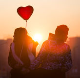 年轻夫妇在爱气球心脏 库存照片