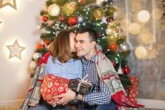 夫妇在爱结合在毯子下在圣诞树附近互相给礼物 免版税库存照片