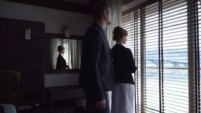 夫妇在现代酒店房间到达了 女孩走向窗口并且看对此,人加入她 股票录像