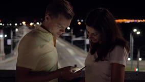 夫妇在看智能手机纸卷的街道上的晚上浏览 影视素材