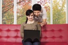 夫妇在秋天在家在网上买 免版税库存图片